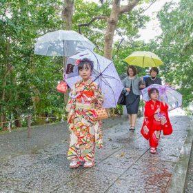 雨の中、傘をさして移動する七五三記念日の家族