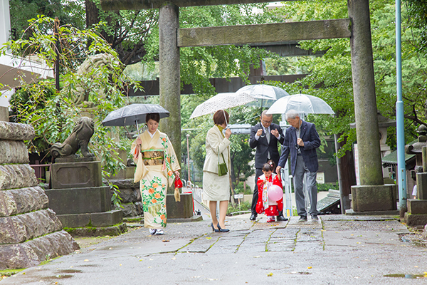東京都新宿区の諏訪神社で傘を差して歩く七五三記念日の家族