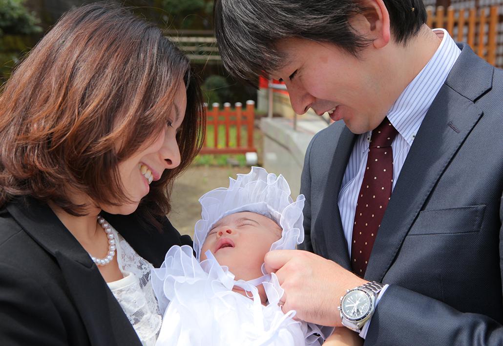 お宮参りの日に赤ちゃんを愛でるパパとママ