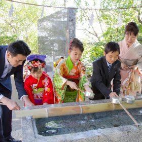 横浜の驚神社でお手水をする七五三記念日の家族