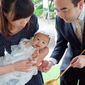 琴平神社で赤ちゃんにお手水をするパパとママ