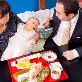 パパにお食い初めをしてもらう赤ちゃん