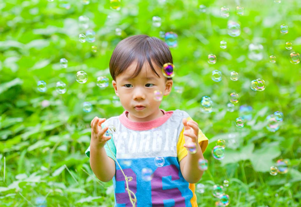 シャボン玉遊びを楽しむ子供の写真